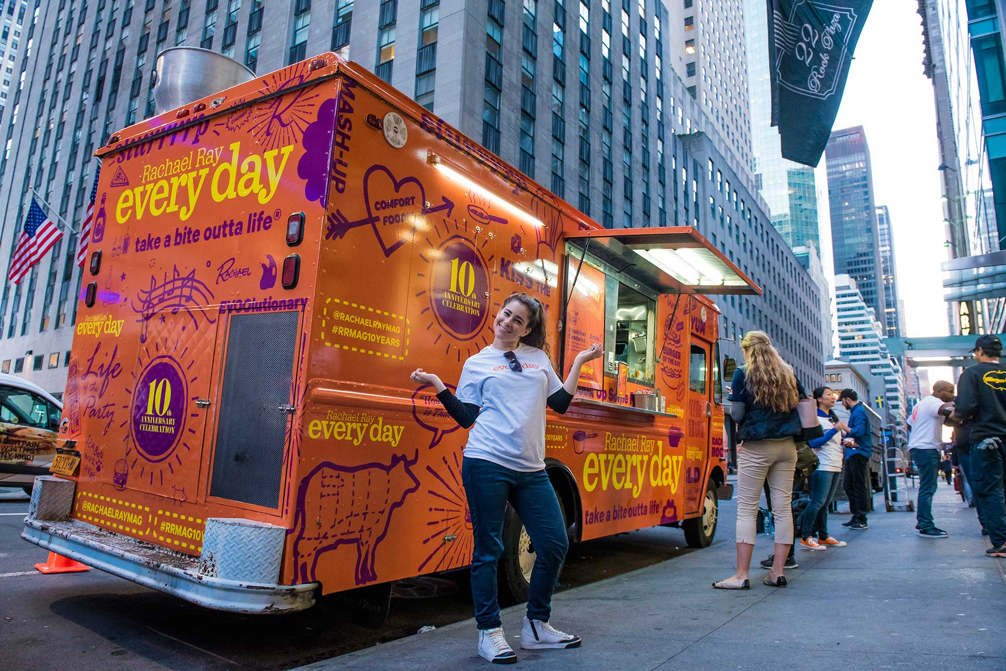 A Brand Ambassador poses with the Rachel Ray Every Day food truck, where guests received free burgers and branded sunglasses.