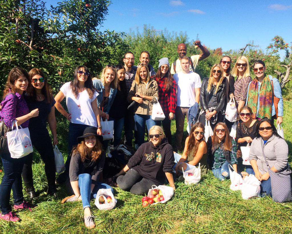 The crew of The Michael Alan Group poses with the apples they gathered at an orchard during MAG's annual Unplugged day.